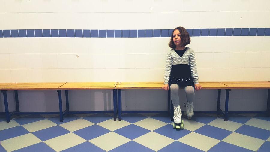 Girl standing against tiled wall