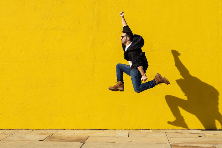 Full length of young woman jumping against yellow wall