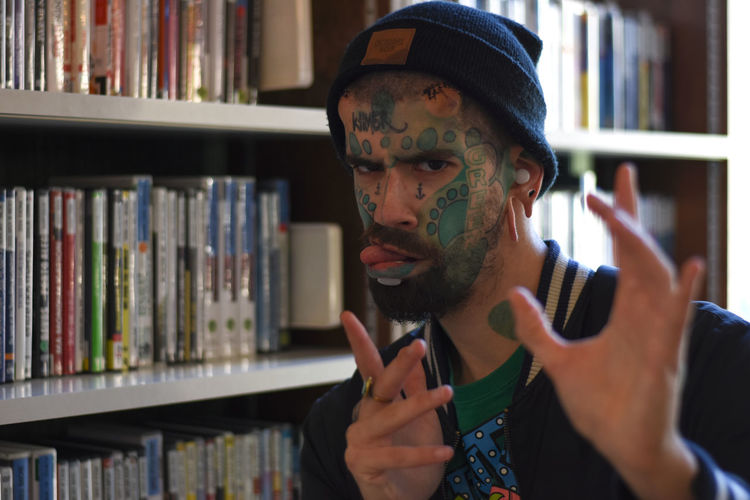 Portrait Of Young Man With Tattoo Gesturing Against Bookshelf At Library