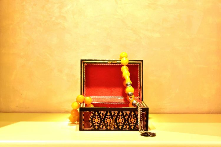 Close-Up Of Jewelry Box On Table Against Wall