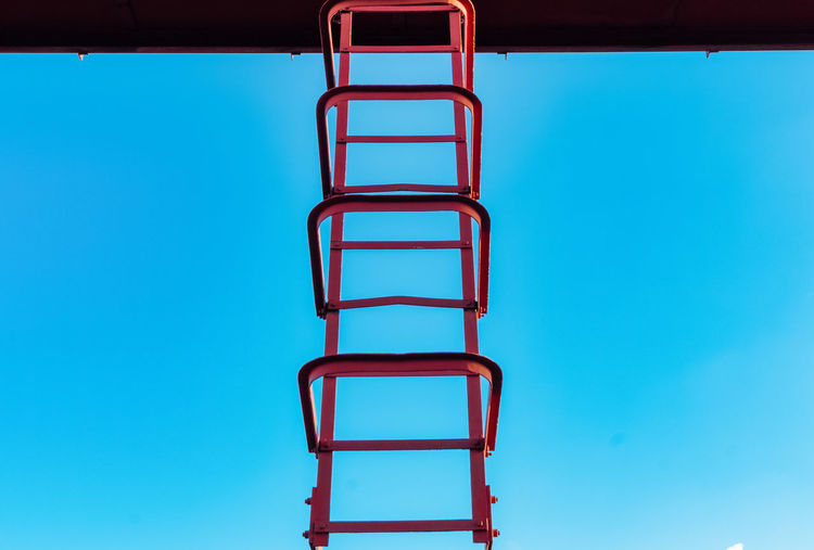 Blue Ladder No People Low Angle View Sky Metal Day Copy Space Clear Sky Built Structure Architecture Nature Staircase Outdoors Red Railing Absence Colored Background Step Ladder Ladder Of Success Blue Background High Up