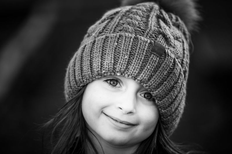 Close-Up Portrait Of Cute Girl In Knit Hat