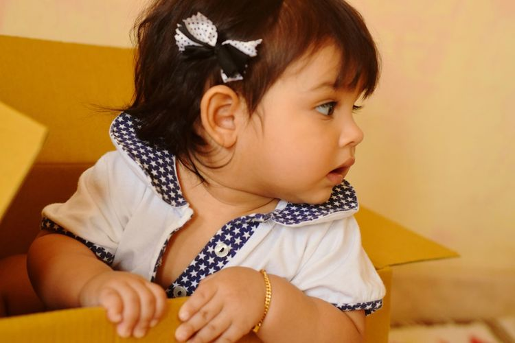 Close-up of cute toddler girl relaxing in cardboard box at home