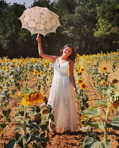 Portrait of woman holding umbrella while standing on sunflower land