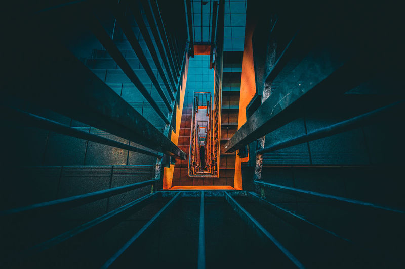 Going Down Architecture Blue Building Building Exterior Built Structure City Diminishing Perspective Empty Illuminated Long Narrow Night No People Outdoors Railing Road Stairs Street The Way Forward Transportation Vanishing Point