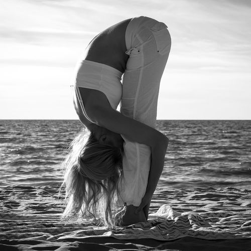 Side view of woman practicing yoga at beach