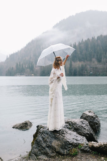 Woman standing by lake with mountain in background