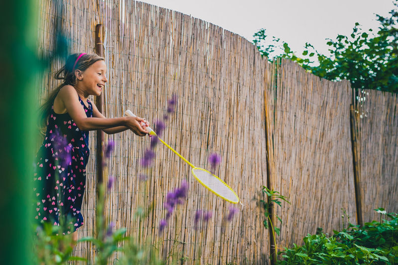 Side view of girl playing badminton in yard
