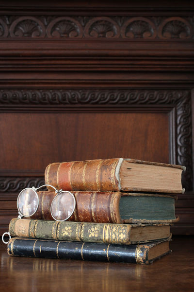 old books piled on a wooden table Antique Books Bookshelf Bookshelfs Learning Library Read Reading Book Close Up Collection Cover Culture Indoors  No People Old Piled Reading A Book Traditional Vertical Wood - Material