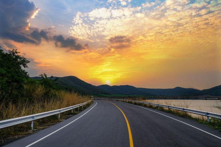 Surface level of road against orange sky