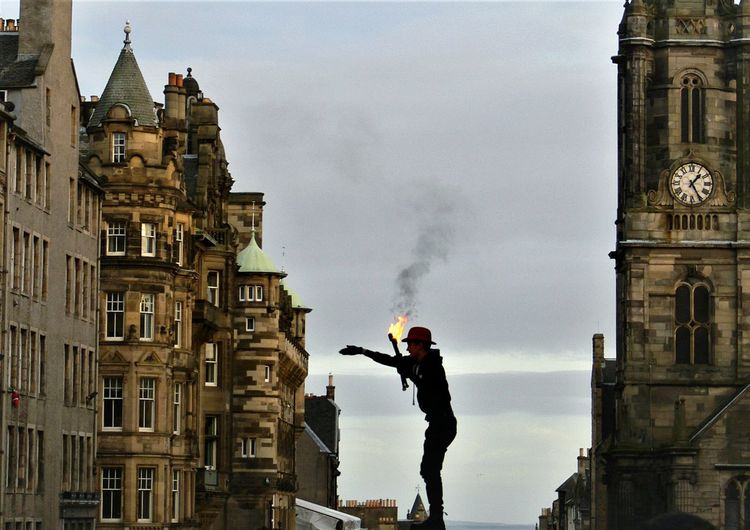 Side view of man with flaming torch gesturing while standing amidst buildings against sky