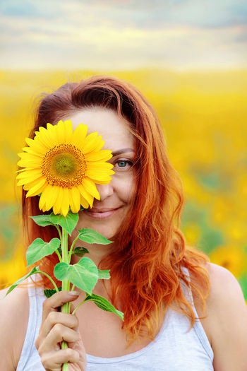 Portrait of beautiful young woman holding yellow dandelion flower