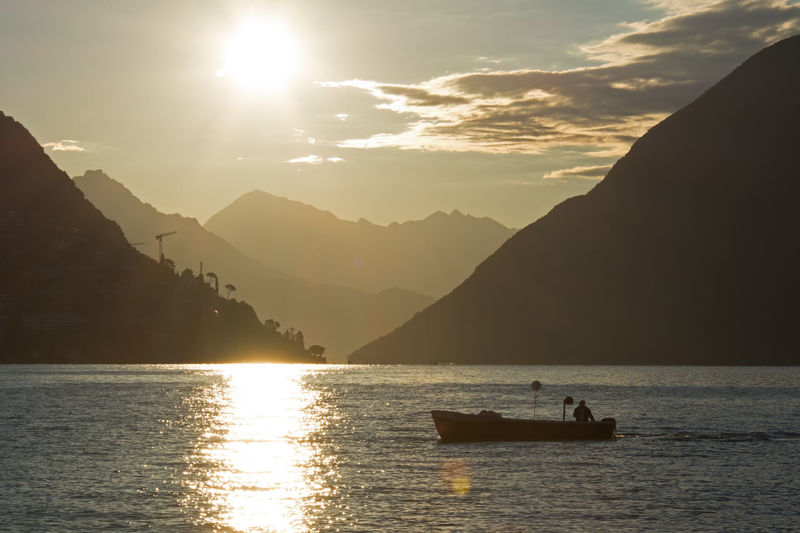 Silhouetted view of boat on river by mountains at disk