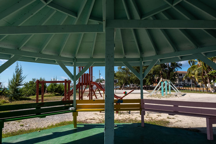Porgy Bay Playground Architecture Built Structure Day Sunlight Nature Tree No People Plant Shadow Outdoors Palm Tree Green Color Tropical Climate Absence Park Park - Man Made Space Metal Architectural Column Building Exterior Seat Outdoor Play Equipment Ceiling