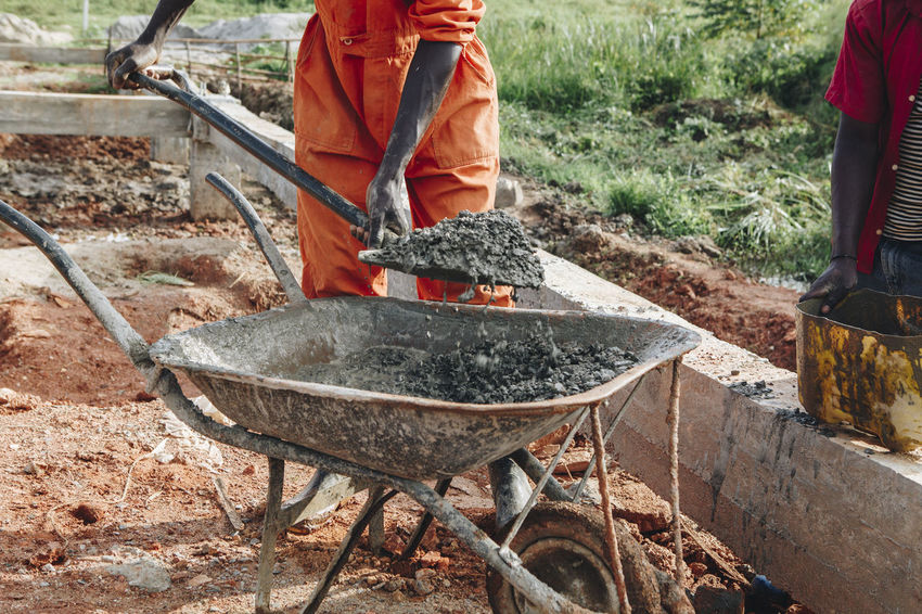 Africa African Building Building Site Concrete Construction Construction Industry Construction Site Construction Work Dirt Dirty Dust Foundations Man Manual Worker Men Mixing Mud Orange Color Protective Workwear Shovel Wheelbarrow Workers Working Working Hard