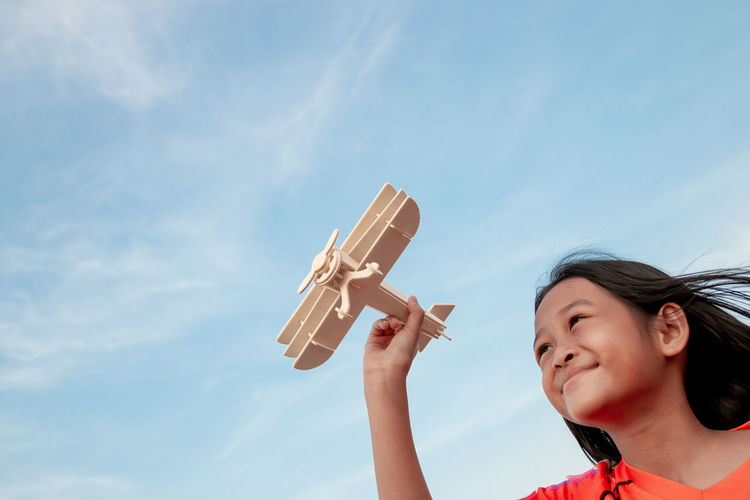 Low angle view of smiling girl playing with model airplane against sky