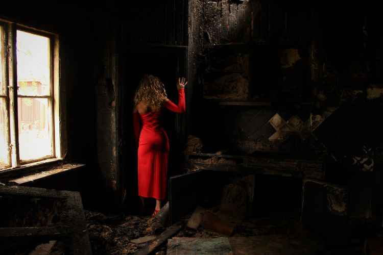 Full length rear view of woman in abandoned room