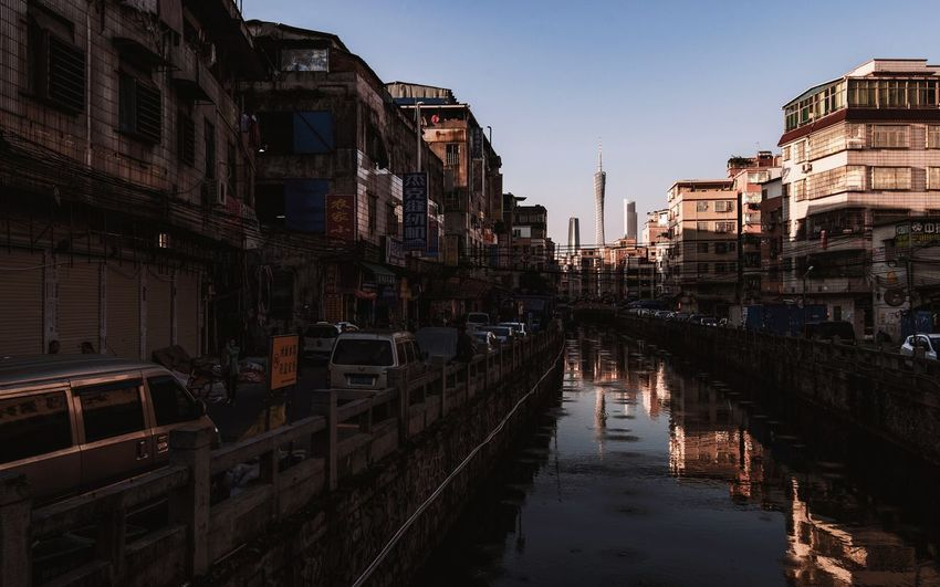 Canal amidst buildings in city against sky at dusk