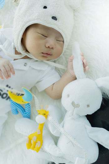 Cute baby boy sleeping with toy on bed at home