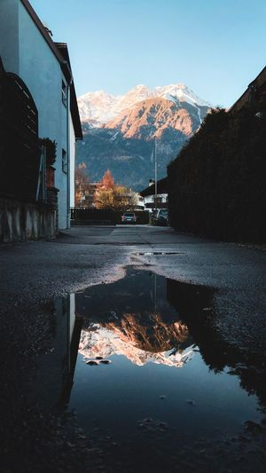 Reflection Of Buildings On Mountain Against Sky