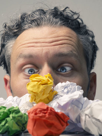 Close-up of surprised man looking at colorful crumpled papers