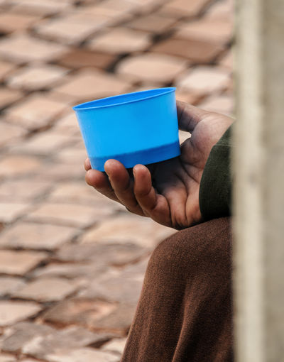 Cropped Hand Of Person Holding Blue Bowl While Begging On Street