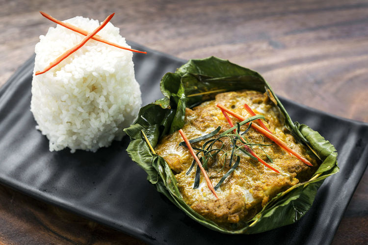 cambodian khmer fish amok curry meal Amok Asian  Cambodian Food Cuisine Curry Famous Cambodian Close-up Day Fish Fish Amok Food Food And Drink Freshness Healthy Eating High Angle View Indoors  Khmer Khmer Food Leaf No People Ready-to-eat Table Traditional