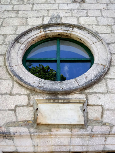 Reflection of blue sky with white clouds and green tree leaf on old church window in Town of Knin Croatia fortress church. Window Frame Window Reflection Blue Sky Blue White Clouds And Blue Sky Green Trea Trea Leaf Tree White Stone White Stone Wall Wall Building Exterior Buildinng Church Architecture Church No People Architecture Window Day Geometric Shape Built Structure Circle Outdoors Nature Wall - Building Feature Low Angle View Shape Reflection Building Old