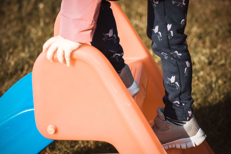 Low section of girl standing on slide at park