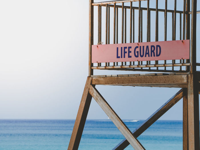 lifeguard hut tower sea side beach Text Western Script Sky Communication Horizon Over Water Sign Wood - Material Sea Water No People Horizon Day Nature Beach Capital Letter Information Information Sign Outdoors Clear Sky Ladder Lifeguard  Lifeguard Hut