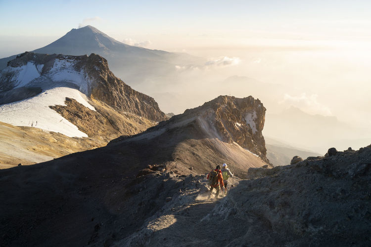 Panoramic shot of people riding on mountain against sky
