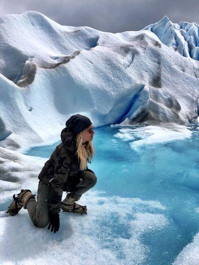 Portrait of mature woman kneeling at glacier