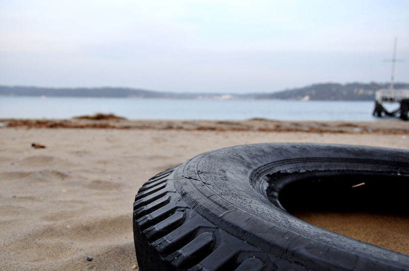Abandoned tire at beach against sky
