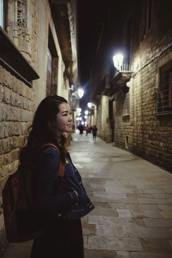 Young woman standing on alley amidst buildings at night