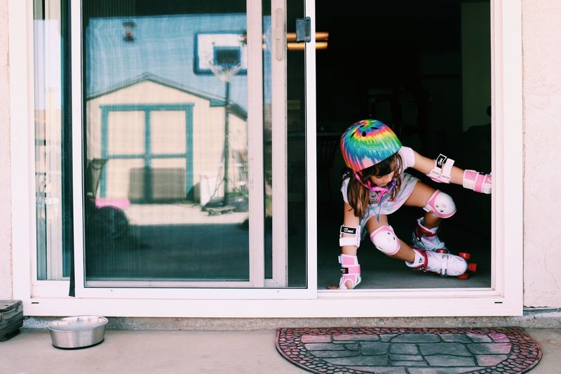 Full length of girl skating in front of door