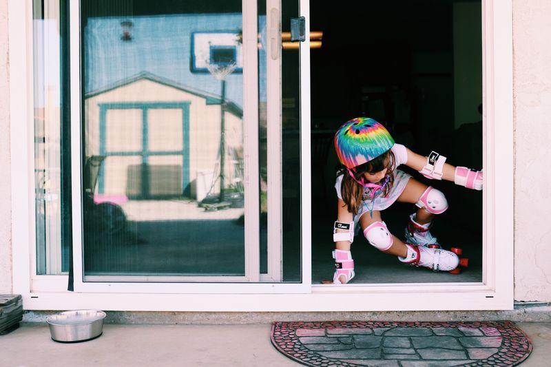 Full length of girl skating in front of door