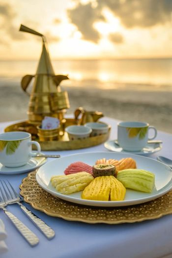 Close-up of dessert with tea cups on table against sea during sunset