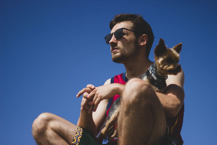Low angle view of man with dog against clear blue sky