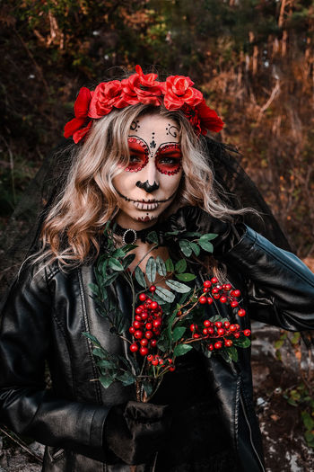 Portrait of woman with red flowers in forest