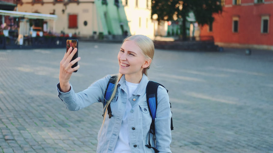 Young woman using phone while standing on street in city