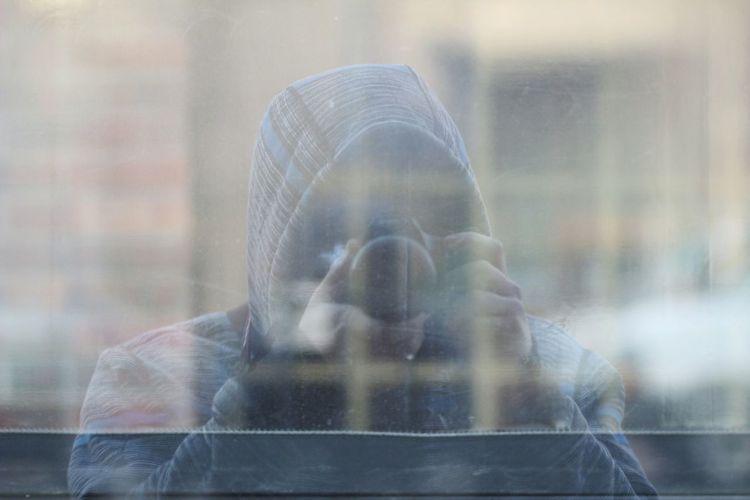 Man taking selfie in window reflection