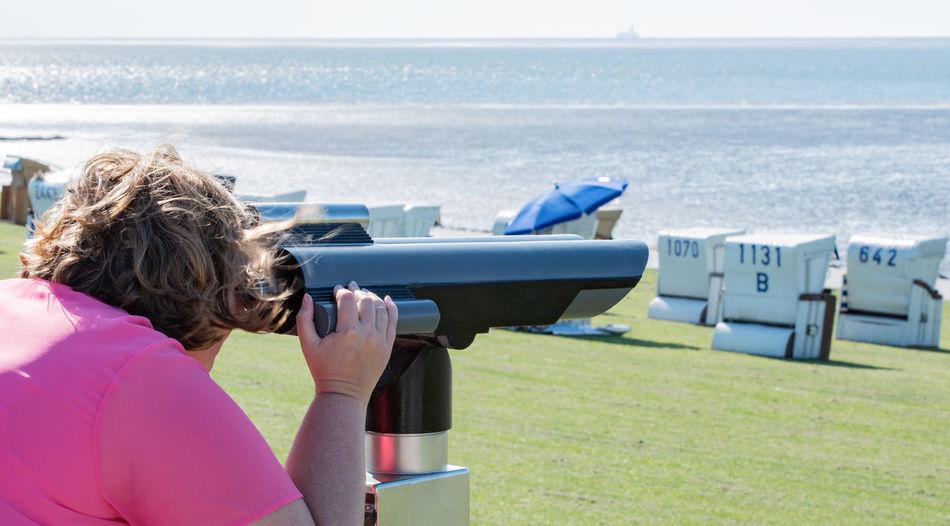 Woman looking at sea through binoculars on field