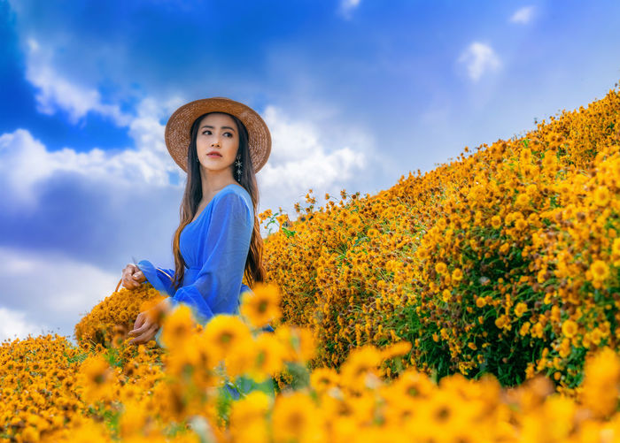 Young woman with yellow flowers against sky