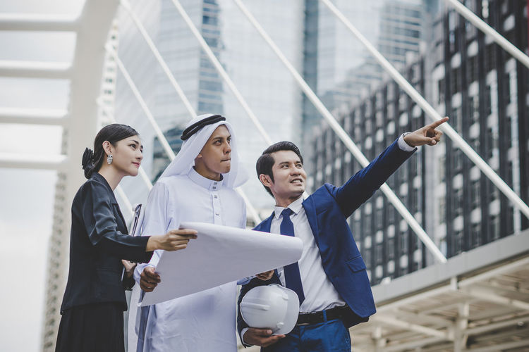 Business people looking at businessman pointing against metallic structure