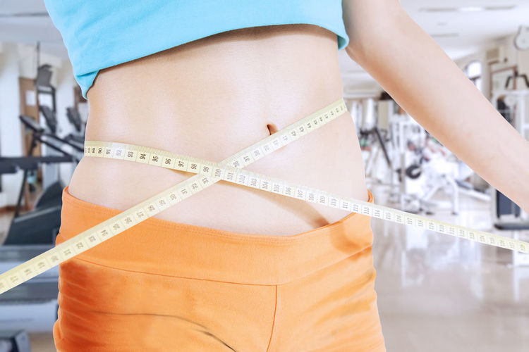 Midsection of woman measuring stomach while standing at gym