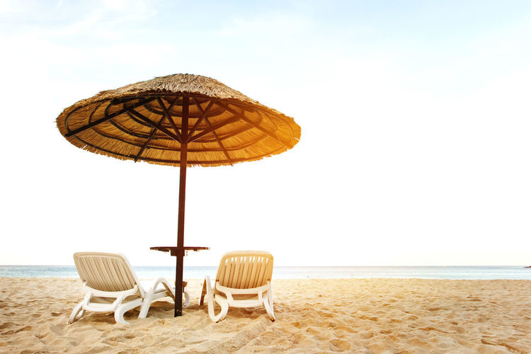 Parasols and chairs on beach against sky
