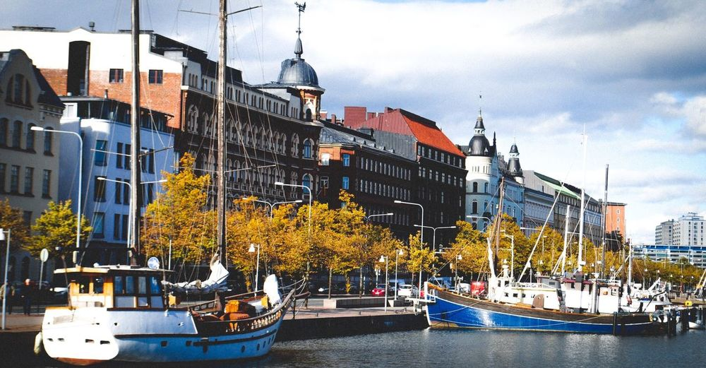 Sailboats moored on river by buildings in city against sky