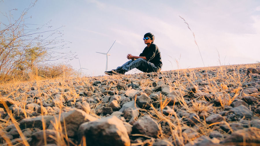 Young man sitting on field against windmills and sky