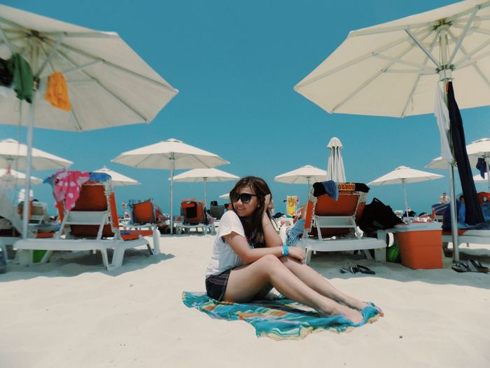 Young Woman Sitting On Towel By Parasols At Beach