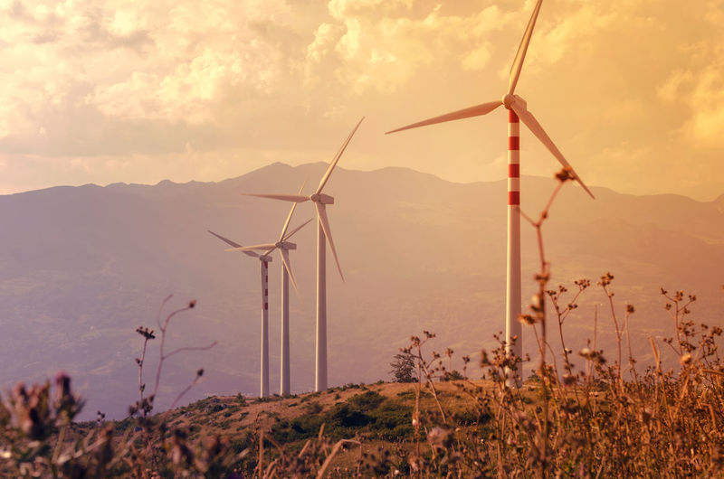 Scenic view of landscape and wind turbines against mountain and  cloudy sky